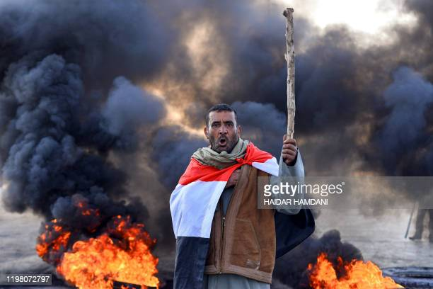 An antigovernment protester draped in a national flag chants slogans while holding a stick at a makeshift roadblock with flaming tyres during a...