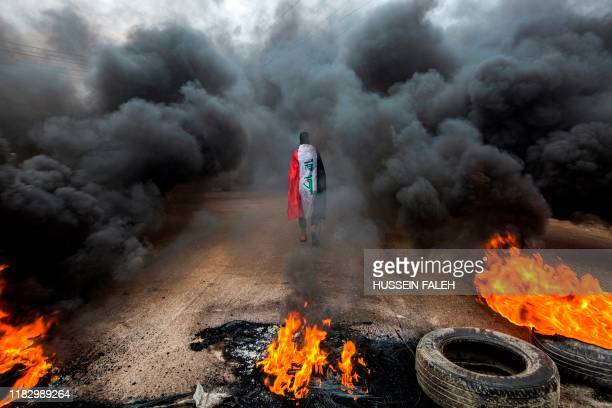 An anti-government protester draped in an Iraqi national flag walks into clouds of smoke from burning tires during a demonstration in the southern...
