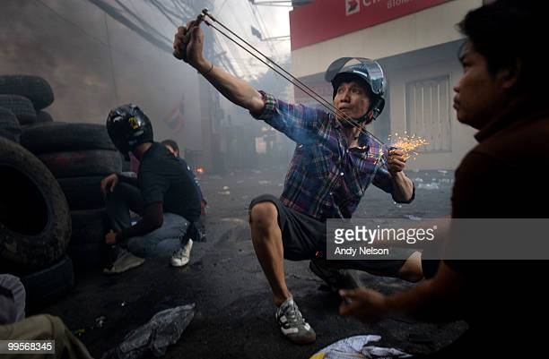 An antigovernment protester fires a firecracker loaded in a slingshot at Thai military forces during street clashes as the violence in central part...
