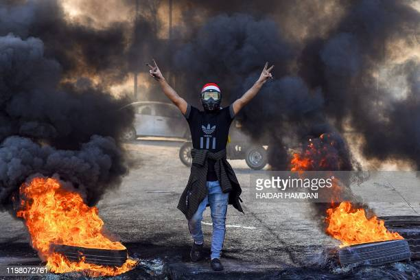 An antigovernment protester flashes the victory gesture by flaming tyres during a protest against the new Iraqi prime minister designate in the...