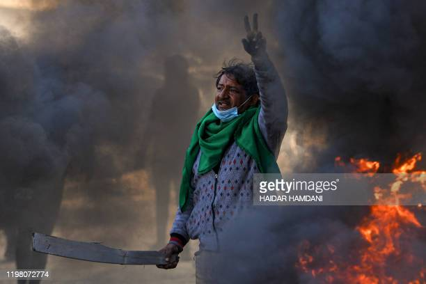An antigovernment protester flashes the victory gesture by flaming tyres during a demonstration against the new Iraqi prime minister designate in the...