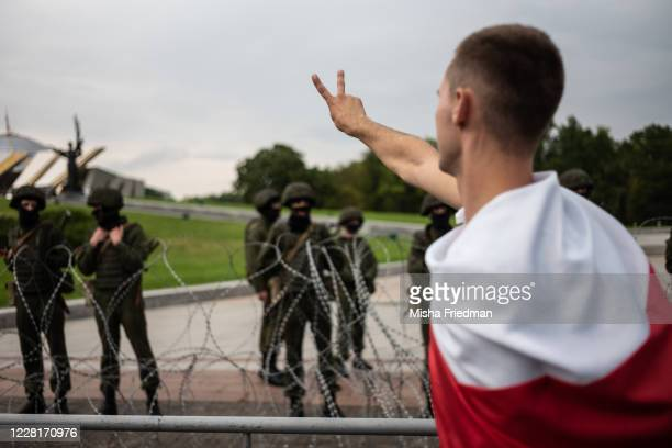An anti-government protester gestures as he walks past riot police and the Belarusian State Museum of the History of the Great Patriotic on August...