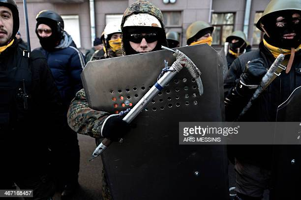 An antigovernment protester holds a shield and a pickaxe as demonstrators march around the Ukrainian Parliament in Kiev on February 6 2014 Ukraine's...