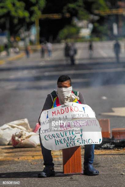 An antigovernment protester holds a sing criticising President Nicolas Maduro sits on the street during a rally ahead of the new Constituent Assembly...