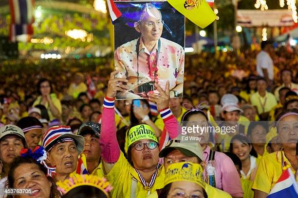 An antiGovernment protester holds up a picture of the Thai King Bhumibol Adulyadej as prayers are said during a mass celebration of his 86th birthday...