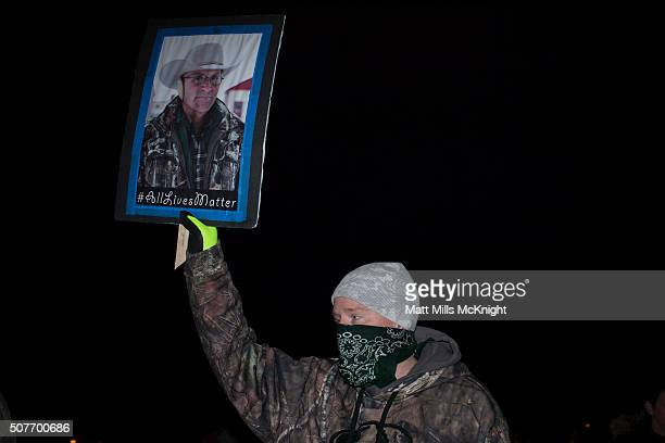 An antigovernment protester holds up a sign during a rally prior to a rolling vehicle protest by selfproclaimed patriots on January 30 2016 in Burns...