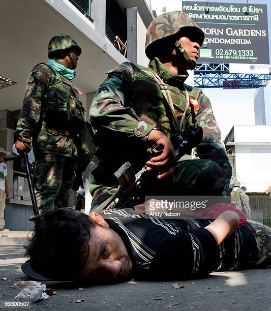 An antigovernment protester is detained by Thai military forces during street clashes on May 14 2010 in Bangkok Thailand Protesters and military...