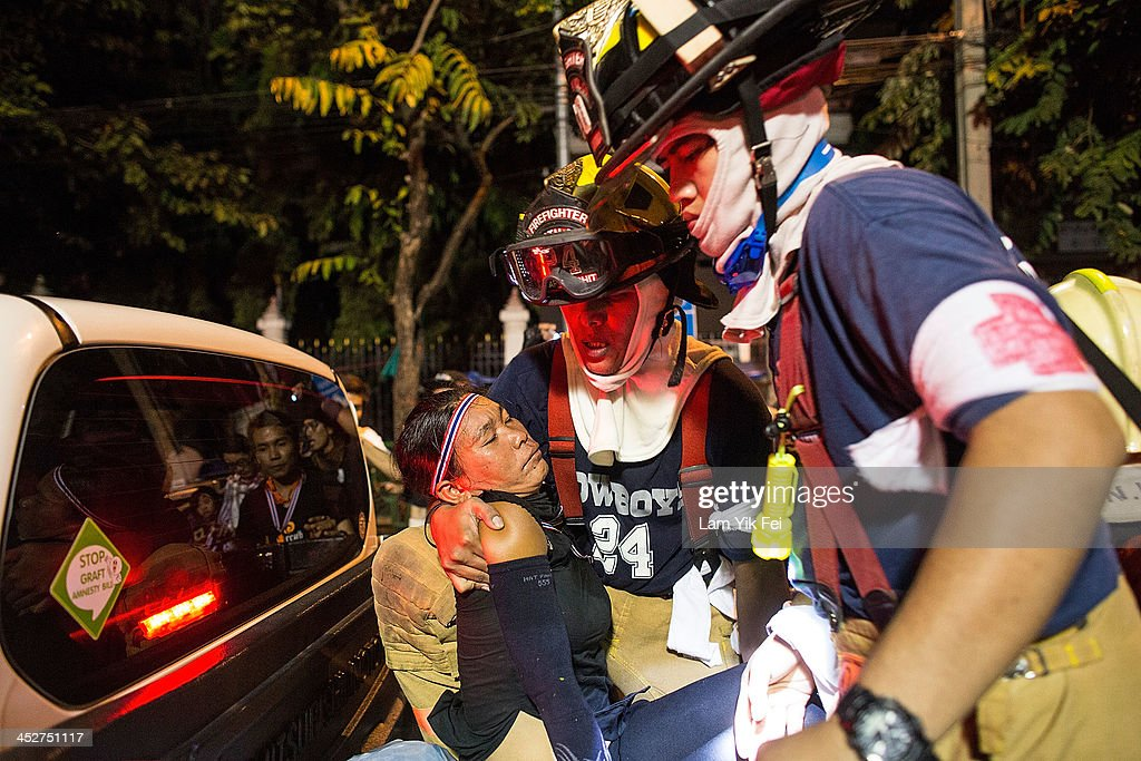 An anti-government protester is helped after being injured after riot police fire tear gas on December 1, 2013 in Bangkok, Thailand. Anti-government protesters in Bangkok say they plan to occupy the government house and the zoo, demonstrators calling on the government to step down have marched on ministries and government bodies in an attempt to shut them down.