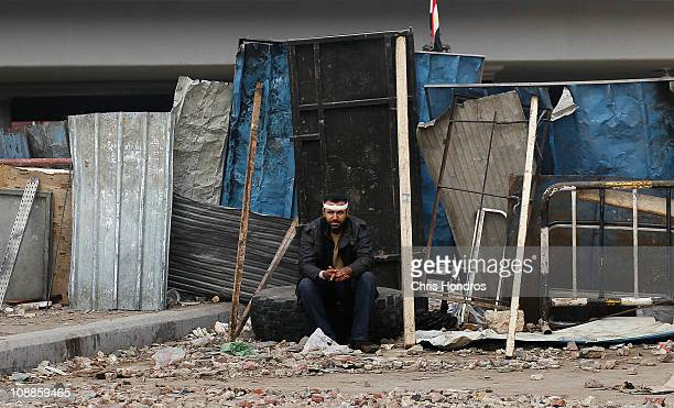 An antigovernment protester leans against makeshift barriers protecting the antigovernment movement in Tahrir Square February 6 2011 in Cairo Egypt...
