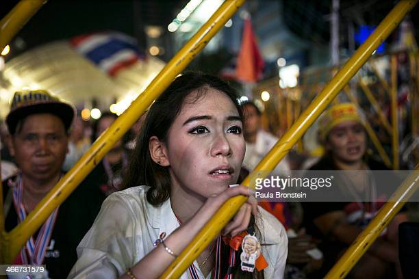 An antigovernment protester listens as leader Suthep Thaugsuban speaks about the elections during his daily speech February 3 2014 in BangkokThailand...