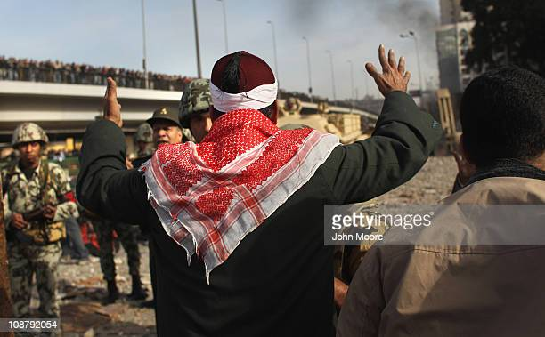 An antigovernment protester pleads with Egyptian army soldiers to stop the violence on February 3 2011 in Cairo Egypt The Army positioned tanks...
