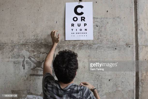 An antigovernment protester puts up a poster accusing corruption in Lebanon's state judiciary on Adlieh roundabout near the offices of Lebanon's tax...