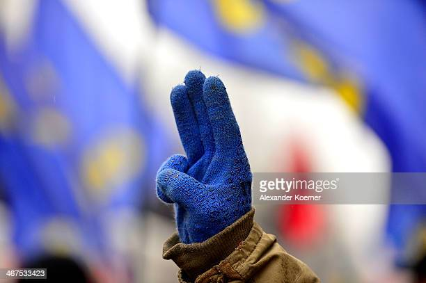 An antigovernment protester raises three fingers while demonstrating through the city centre on February 07 2014 in Kiev Ukraine Although parliament...