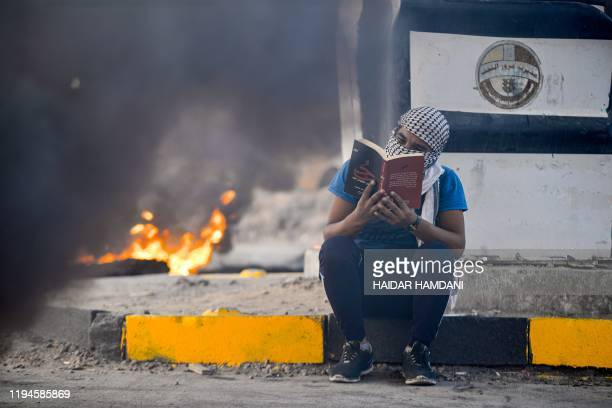 An anti-government protester reads a novel as he sits on the pavement near a tire fire during a demonstration in the central Iraqi holy shrine city...