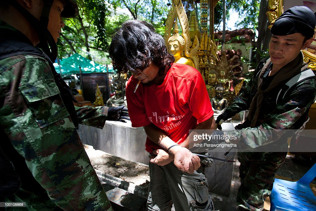 An anti-government protester 'Red Shirt' is detained by Thai security forces at Temple near their encampment on May 21, 2010 in Bangkok, Thailand. Thai Prime Minister Abhisit Vejjajiva says order has been restored to the capital Bangkok and throughout the country. A night-time curfew remains in place in Bangkok and 23 provinces are to prevent a resurgence of unrest. At least 44 people have been killed in clashes in which protesters clashed with military forces over a period of six consecutive days, resulting in the end of the blockade and the surrender of Red-shirt leaders.