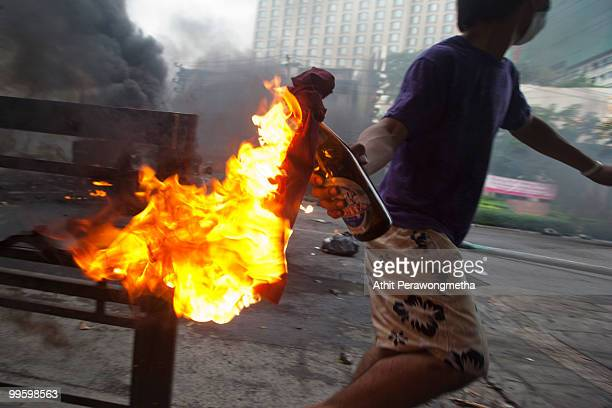 An antigovernment protester 'Red Shirt' throws a molotov cocktail toward Thai security forces as the violence in central Bangkok continues on May 16...