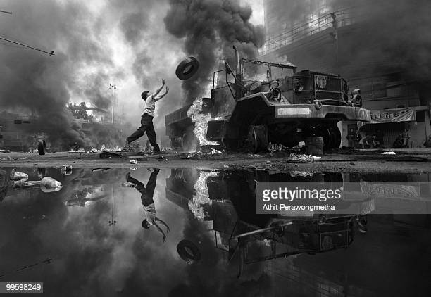 An antigovernment protester 'Red Shirt' throws a tire toward a burned truck as the violence in central Bangkok continues on May 16 2010 in Bangkok...