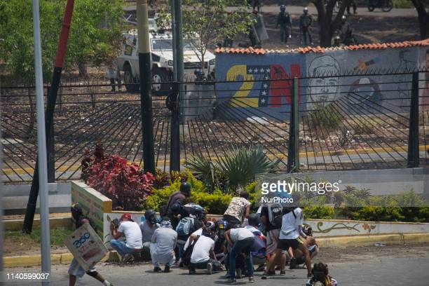 An antigovernment protester runs during clashes with security forces in the surroundings of La Carlota military base in Caracas during the...