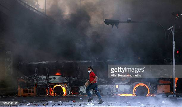 An antigovernment protester runs past a bus torched by supporters of former Prime Minister Thaksin Shinawatra during a protest on April 13 2009 in...