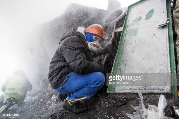 An antigovernment protester shields himself water sprayed by police near Dynamo Stadium on January 25 2014 in Kiev Ukraine Violent protests in...