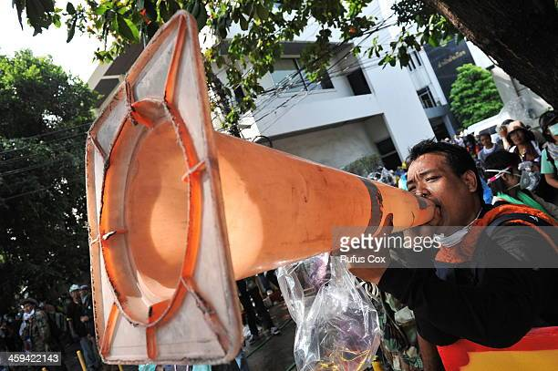 An antigovernment protester shouts slogans into a traffic cone while taking part in a violent protest at a sports stadium where the Thai Election...