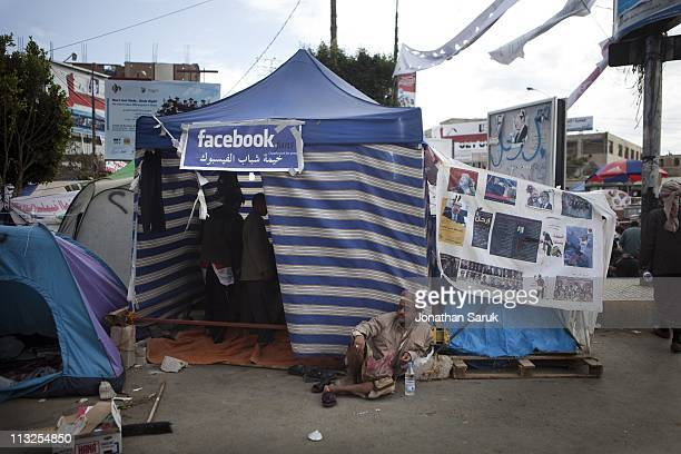 An antigovernment protester sits near an internet tent after clashes with progovernment supports near the University of Sana on March 13 2011 in Sana...