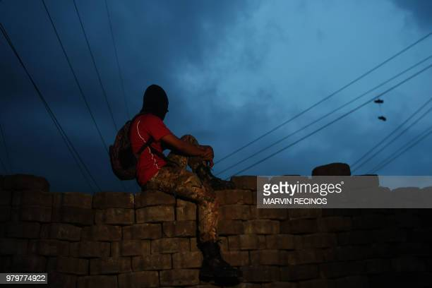 TOPSHOT An antigovernment protester sits on a a barricade in Managua on June 20 2018 Nicaraguan President Daniel Ortega has taken advantage of failed...