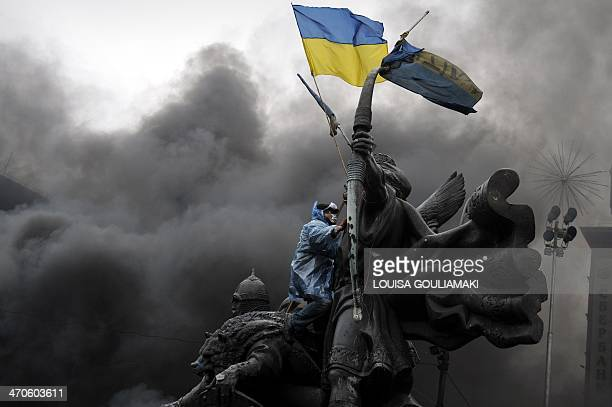 An antigovernment protester sits on the Founders of Kiev monument during clashes with riot police in central Kiev on February 20 2014 At least 25...