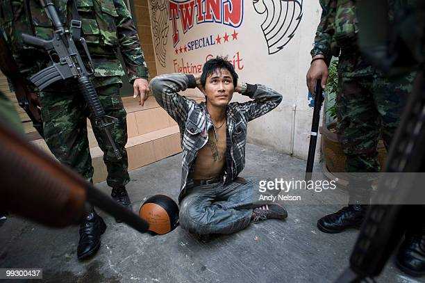 An antigovernment protester sits on the ground while being detained by Thai military forces during street clashes on May 14 2010 in Bangkok Thailand...