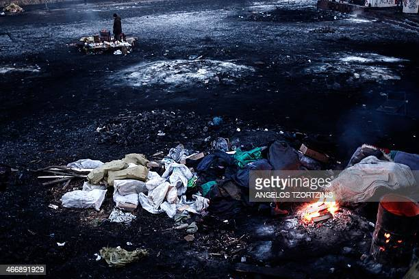An antigovernment protester stands next to a bonfire near a barricade early on February 5 2014 in Kiev Ukraine's parliament will try again on...