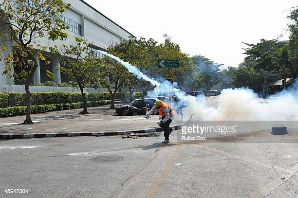 An antigovernment protester throws a policefired tear gas canister back at a police during a violent protest at a sports stadium where the Thai...