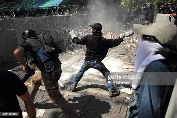 An antigovernment protester throws a water bottle at police during a street battle to occupy Government House in Bangkok Riot police fired tear gas...