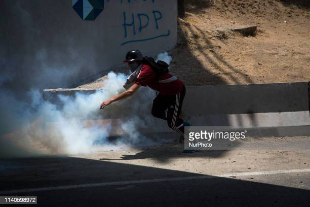 An antigovernment protester throws Molotov cocktails during clashes with security forces in the surroundings of La Carlota military base in Caracas...