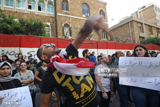 An antigovernment protester throws tomatoes at Lebanon's Central Bank headquarters at the same time of a press conference held by the bank's governor...