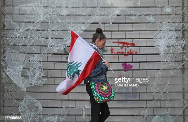An anti-government protester walks with a Lebanese national flag past a broken window in downtown Beirut on October 24, 2019 amidst ongoing protests...