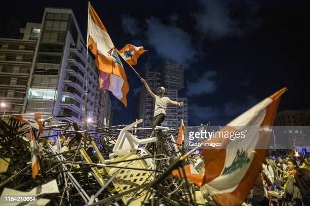 An anti-government protester waves a Lebanese flag as he stands on top of a pile of broken tents in Martyrs' Square on October 29, 2019 in Beirut,...