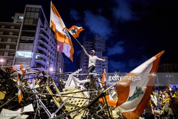 An antigovernment protester waves a Lebanese flag as he stands on top of a pile of broken tents in Martyrs' Square on October 29 2019 in Beirut...
