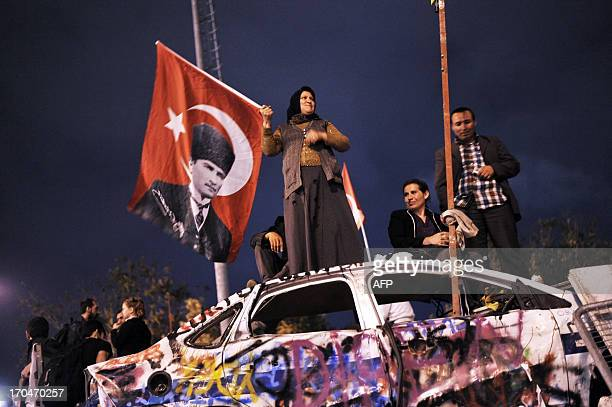 An antigovernment protester waves a Turkish flag with a poster of Mustafa Kemal Ataturk founder of modern Turkey at Taksim Gezi park in Istanbul on...