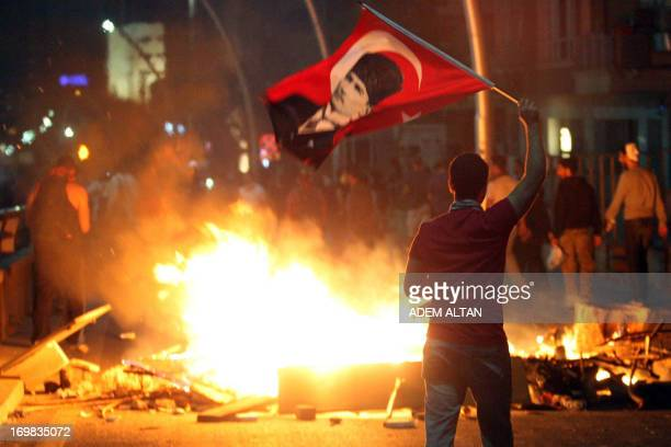 An antigovernment protester waves Turkey's national flag bearing a portrait of Mustafa Kemal Ataturk founder of modern Turkey during a demonstration...