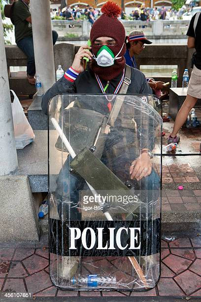 An anti-government protester wears a gas mask and holds on to a stolen police riot shield at a demonstration outside Bangkok's central police...