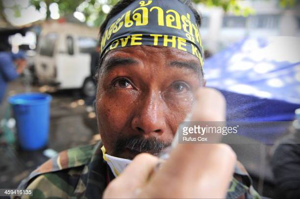 An anti-government protesters overcome by tear gas has his eyes rinsed with saline during a violent protest at a sports stadium where the Thai...