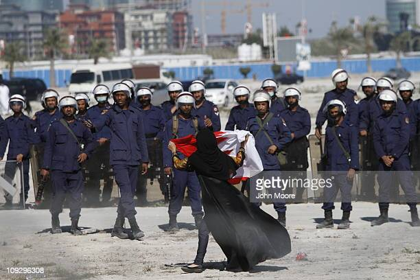 An antigovernment protestor gestures in front of police as demonstrators reoccupy Pearl roundabout on February 19 2011 in Manama Bahrain...