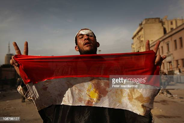 An anti-government protestor holds a blooded Egyptian flag in Tahrir Square on February 3, 2011 in Cairo, Egypt. The Army have positioned tanks...