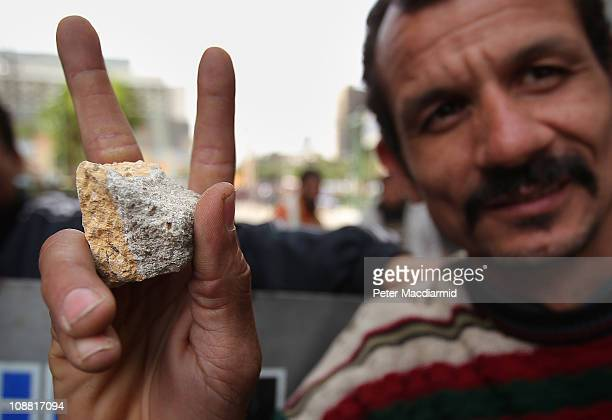 An antigovernment protestor shows a victory sign as he holds a stone in Tahrir Square on February 4 2011 in Cairo Egypt Antigovernment protesters...