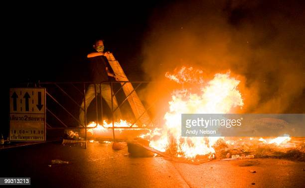 An antigovernment Red Shirt protester adds to a burning barricade in the streets on May 14 2010 in Bangkok Thailand So far more than 100 people have...