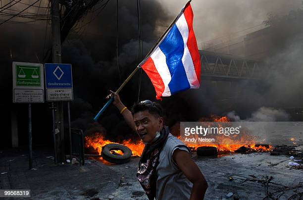 An antigovernment red shirt protester flies the Thai flag after advancing up a street during street clashes as the violence in central part of the...