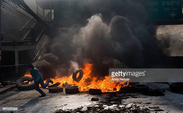 An antigovernment red shirt protester seeks cover after adding to a burning pile of tires during street clashes as the violence in central part of...