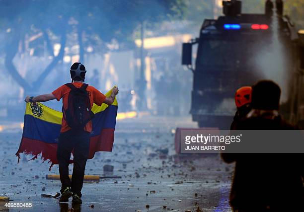 An antigovernment student holding a tore Venezuelan flag stands in front of a water cannon during a protest in Caracas on February 15 2014 Supporters...