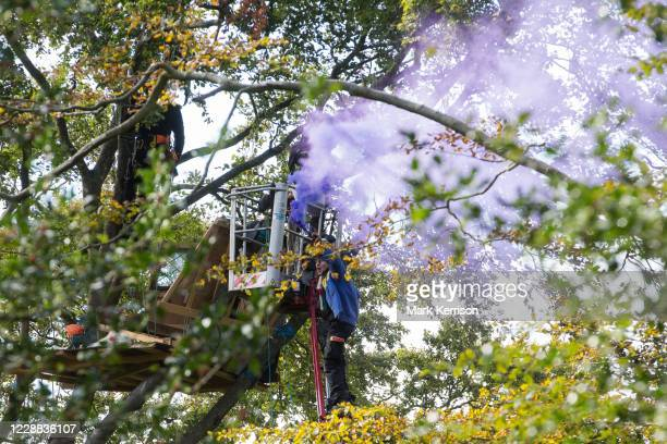 An antiHS2 tree protector with a smoke grenade climbs onto the arm of a cherry picker being used by National Eviction Team bailiffs working on behalf...