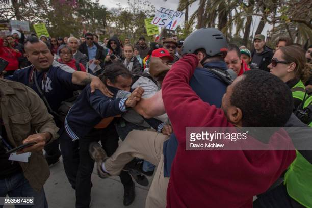 An antiimmigrant protester wearing a helmet and draped with an American flag fights with Latino marchers on May Day on May 1 2018 in Los Angeles...